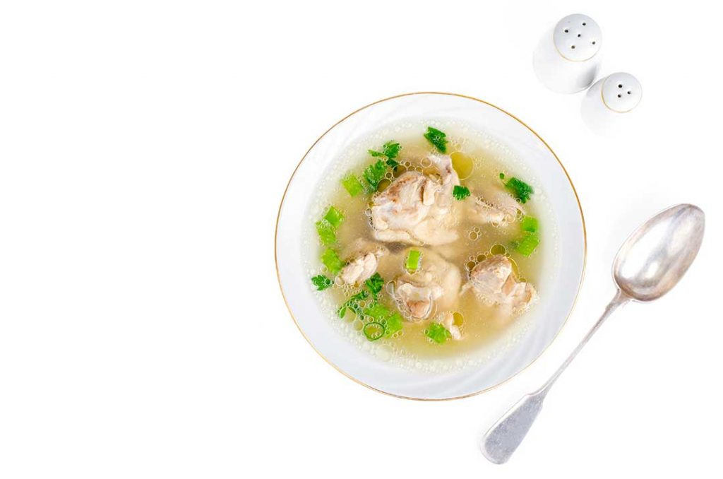 broth with chicken meat isolated on white peq